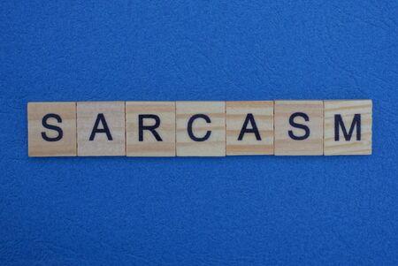 Sarcasmo palabra hecha de letras de madera gris se encuentra sobre un fondo azul.