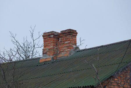 two brown old chimneys on a slate green roof against a gray sky Stock fotó - 134778404