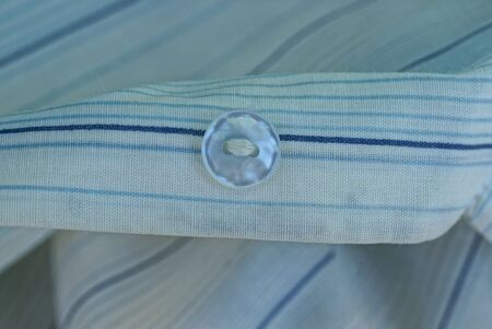 one small white plastic button on a striped cloth