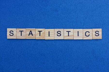 word statistics made from wooden gray letters lies on a blue background