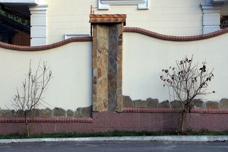 large private fence of gray concrete and brown stones in the wall on the street
