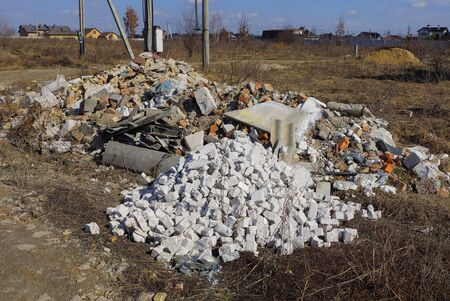 piles of garbage made of white bricks and stones in gray dry grass in a field on nature