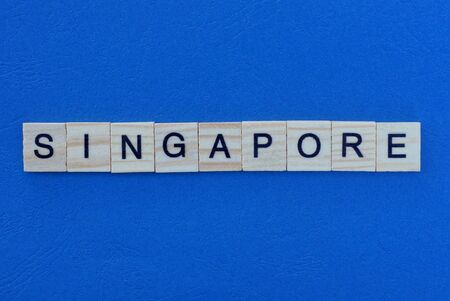 word singapore from wooden gray letters lies on a blue background