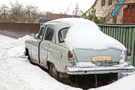 one retro car in gray under a snowdrift of snow on the street