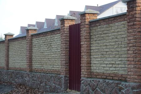 brown private brick fence and closed metal door