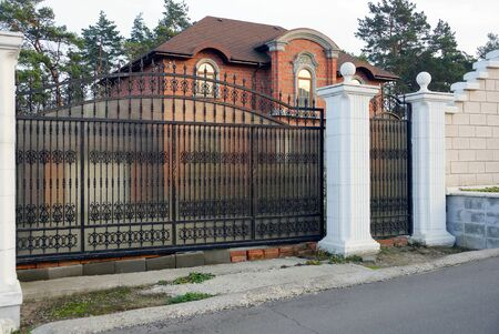 black iron gate with forged pattern and white brick fence on the street