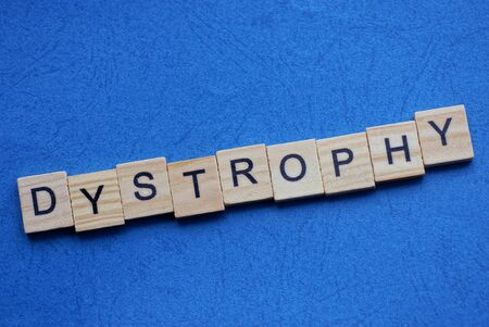 word dystrophy made from wooden letters lies on a blue table 스톡 콘텐츠