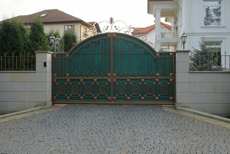 large iron green gate with a brown forged pattern and a gray brick fence on the sidewalk