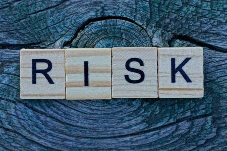 word risk made from wooden letters lies on a gray background