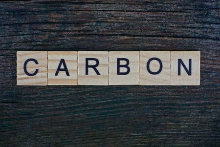 word carbon made from wooden gray letters lies on a gray background