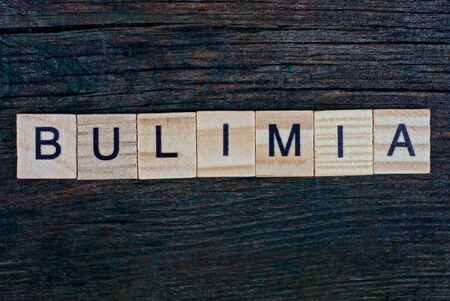 word bulimia made from wooden gray letters lies on a gray background 스톡 콘텐츠