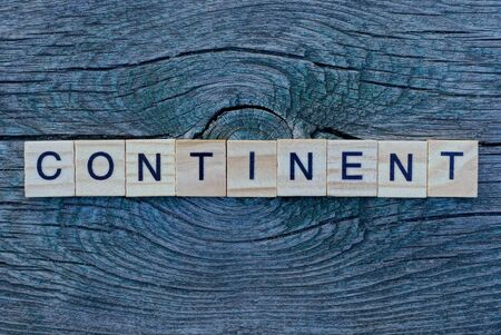 word continent made from wooden gray letters lies on a gray background