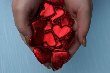 Red small hearts in the palms of hands on a blue background