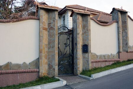 black iron door with forged pattern and gray concrete fence on the street