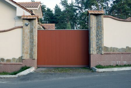 brown iron gate and gray concrete and stone fence in the street 스톡 콘텐츠