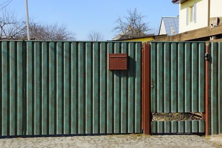 closed green door on a private metal fence on the street
