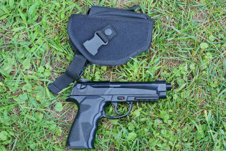 one black gun in a holster lies on the green grass outside