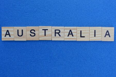 word australia made from wooden letters lies on a blue table