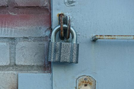 one large gray padlock on an iron gate and a brick wall