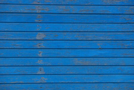 blue wooden texture of thin frayed boards in the wall of the fence