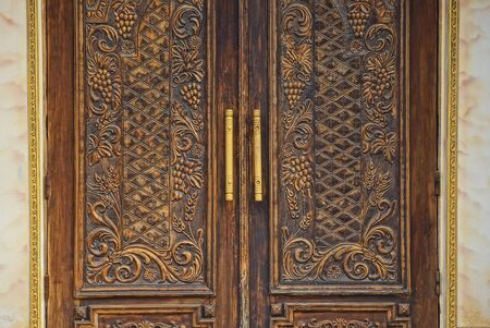 old brown wooden door with a pattern on a gray concrete wall