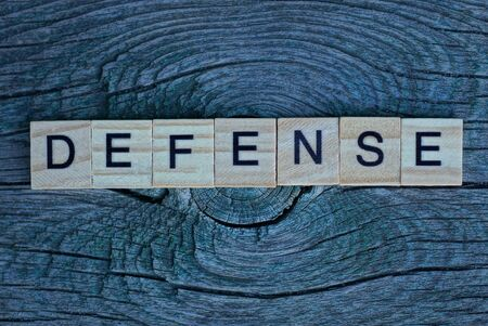 word defense from small letters lies on a gray wooden board