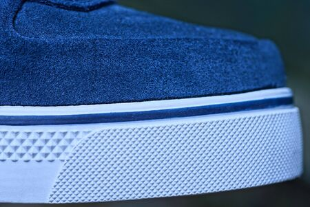 part of the shoe made of blue suede and white plastic sole