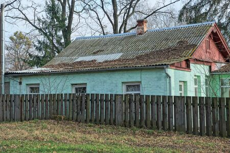 rural house with a green brick wall and windows under a gray slate roof behind a wooden fence