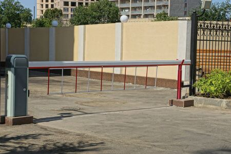 closed barrier on a city street near a brown fence