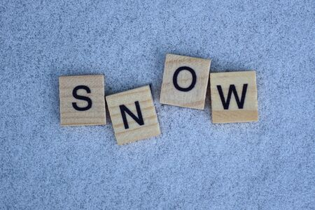 word made of small gray wooden letters lies on white snow