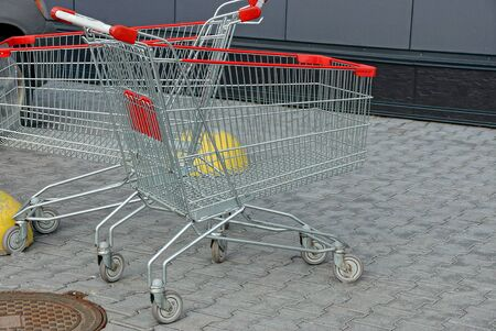 two empty gray metal empty trolleys with red handles on wheels stand on the sidewalk on the street against the wall
