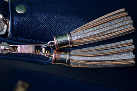decor of two brown gray tassels on a lace zip made of leather and metal on a blue bag