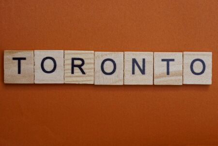 gray word toronto from small wooden letters on a brown table Stock fotó