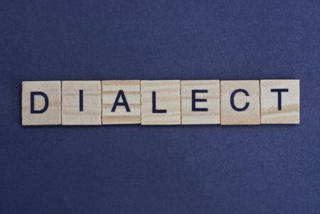 gray word dialect from small wooden letters on a black table Stok Fotoğraf