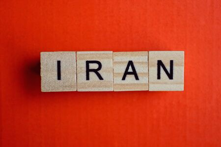 word iran made of small gray wooden letters on a red paper background