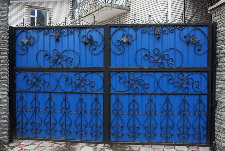 large closed colored gates of iron black forged bars in a pattern on a blue metal wall on the street Stock Photo