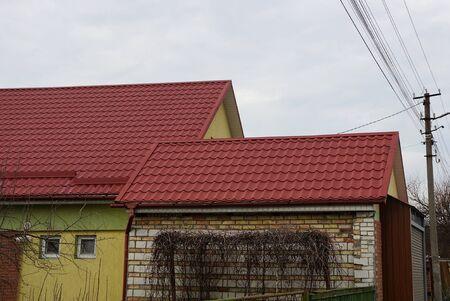 Teil eines gemauerten Privathauses mit Dachboden unter rotem Ziegeldach vor grauem Himmel
