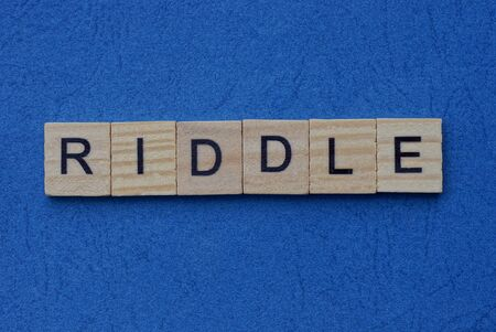 gray word riddle from small wooden letters on a blue table