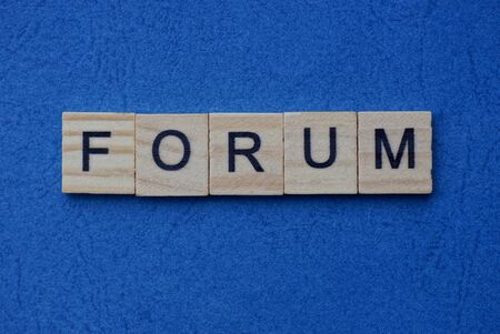 gray word forum from small wooden letters on a blue table