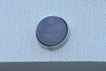 one gray round glass lantern on a white concrete wall of a building on the street Standard-Bild - 140257626