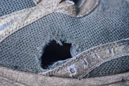 one big black hole on the gray fabric of an old sneaker