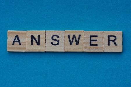 gray word answer from small wooden letters on a blue table