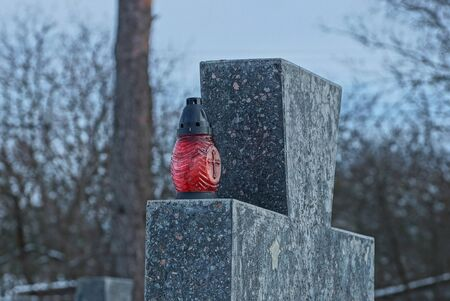 one red glass lamp stands on a gray marble cross in a cemetery against a blue sky