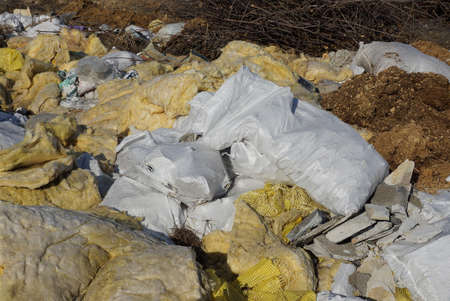 garbage from white bags and pieces of yellow glass wool in a heap in nature on a sunny day