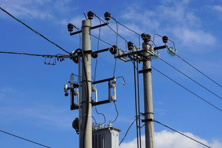 two gray concrete pillars with electric wires on a background of blue sky and clouds on a sunny day