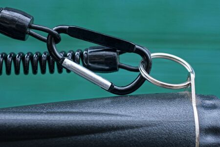 black metal carabiner clasp on a plastic wire on a green background