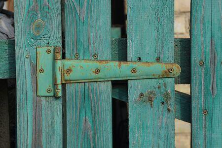 one green iron door hinge in rust on wooden boards door on the street Reklamní fotografie