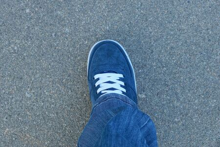 leg in blue jeans and a suede sneaker with white lace stands on the gray asphalt on the street