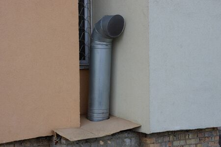 one gray metal fan pipe near the brown concrete wall of the house 写真素材