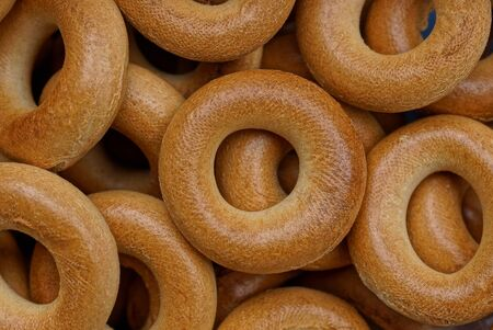 brown background of small round bagels in a heap